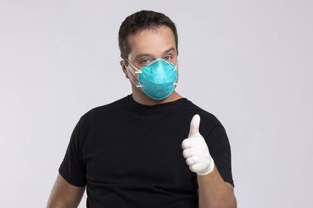 Man in a mask and surgical gloves gives a thumbs up.