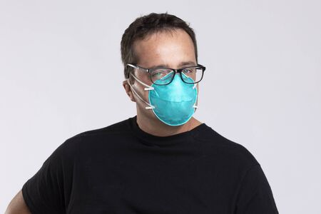 Man with spectacles in N95 surgical mask.