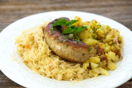 Roasted sausages with sauerkraut and potatoes Stock Photo