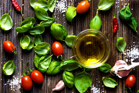 cooking oil: Fresh basilic leaves on a wooden table. Stock Photo