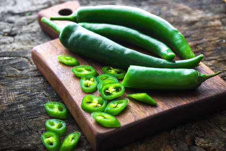green chilli: Fresh green chilli on old wooden background Stock Photo