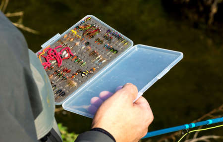 flyfishing: Fly fisherman  chooses a fly for flyfishing trout Stock Photo