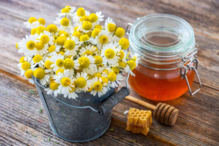 Chamomile flowers and honey on wooden background