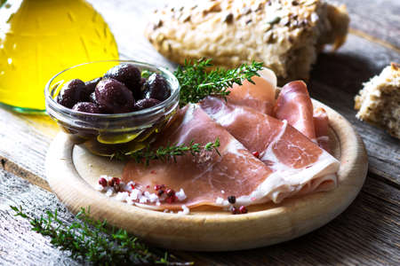 Thin slices of prosciutto with  olives on wooden background Stock Photo