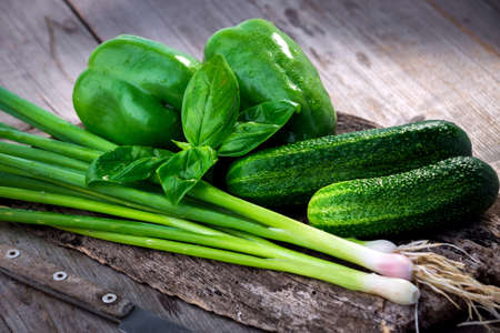 Fresh green vegetables on wooden background