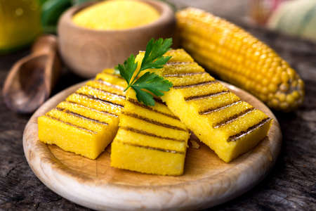 Grilled polenta on old wooden background
