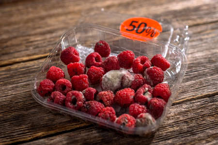 Raspberry in a plastic box bought on sale Stock Photo
