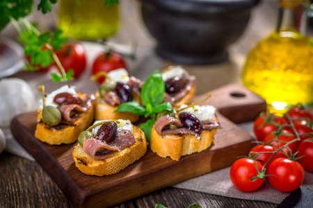 caper: Tasty bruschetta with anchovy,  feta, caper, olive oil ... Stock Photo