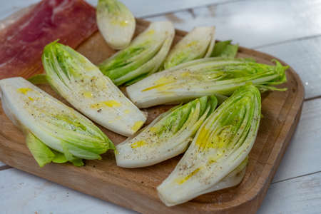 Fresh Chicory Salad on rustic wooden table. Stock Photo