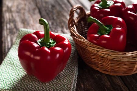 Fresh red peppers on wooden background Standard-Bild