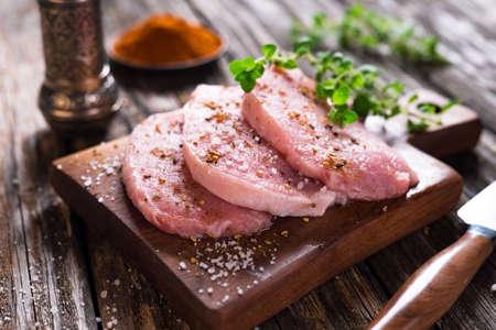 Juicy  pork steaks  on  wooden background Standard-Bild