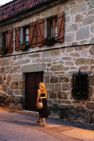 Woman walking on a stone street at night Standard-Bild