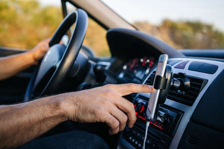 Man using phone with hand while driving a car