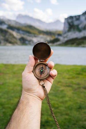 A hand holds a compass in a mountain and lake landscape Foto de archivo