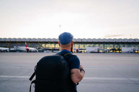 A man gets on the plane from the runway down the stairs