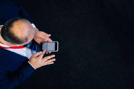 Aerial view of a man using a mobile phone on a black floor Stock Photo