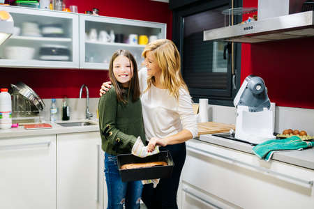 A mother with her daughter in the kitchen at home preparing a cake together as a family