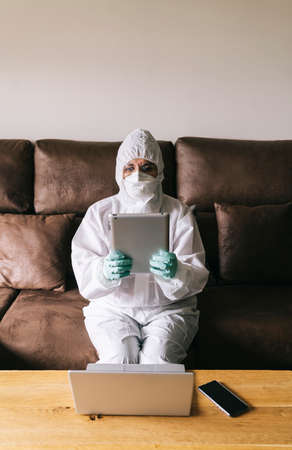 A woman works from home with the laptop, digital tablet and mobile phone in the living room, equipped with security measures against a virus prevention with a safety suit, glasses, mask and latex gloves.