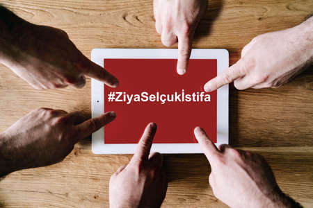 group hands point the screen of a digital tablet with the text of the hastag ZiyaSelçukÄ°stifa Minister of National Education Turkish Stok Fotoğraf