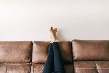 a woman's legs raised up high on the brown sofa at home