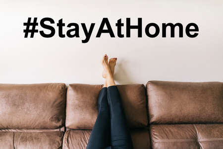 a woman's legs raised up high on the brown sofa at home. Hastag, with a message to stay home