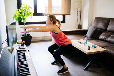 beautiful blonde caucasian athlete woman doing exercises with elastic band in living room at home