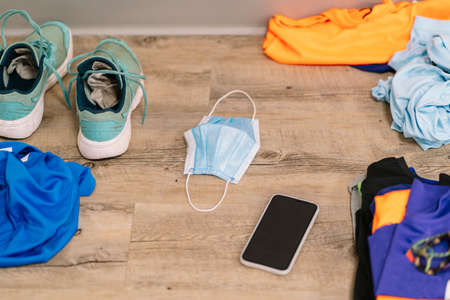 A mask with clothes and shoes and a mobile phone on the floor of a gym 스톡 콘텐츠
