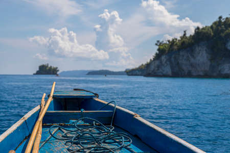 rudimentary blue boat in the middle of the sea in front of a small island, travel concept