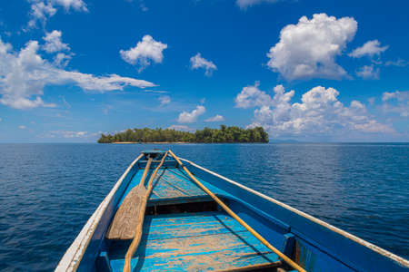 rudimentary blue boat in the middle of the sea in front of a small island with a blue sky and clouds.