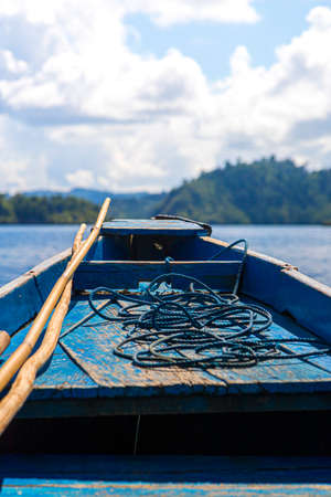rudimentary blue boat in the middle of the sea in front of a small island, travel concept. vertical