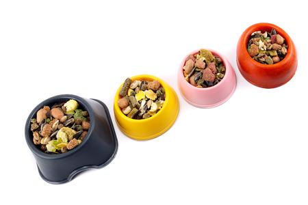 Una variedad de alimentos granulados nutritivos y equilibrados para roedores en tazones aislados sobre fondo blanco.
