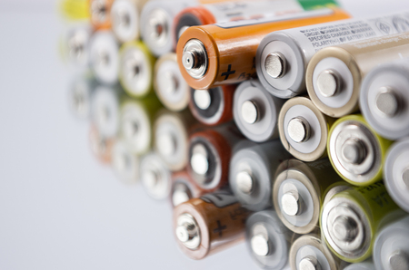 alkaline AA batteries on the glass surface with close-up reflection, salt batteries, accumulators