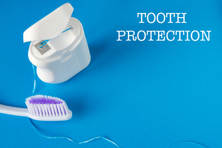 dental floss and toothbrush on a blue background, the concept of care for the oral cavity, preventing tooth decay, copyspace
