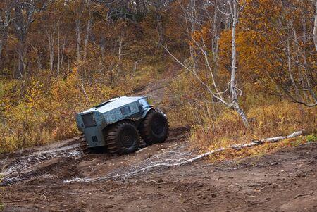 Vehículo todo terreno con grandes ruedas que supera una carretera sucia. Foto de archivo