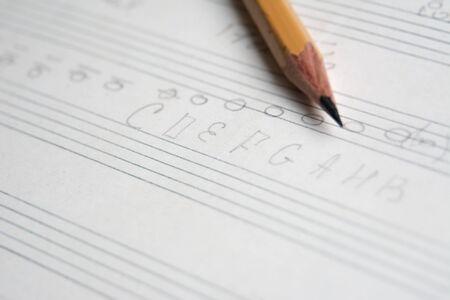 Lápiz en un primer plano de cuaderno musical, notas y acordes musicales abstractos, fondo musical