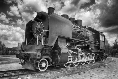 treno a vapore d'epoca che sfreccia a velocità lungo i binari ravvicinati, veicolo retrò, motore a vapore