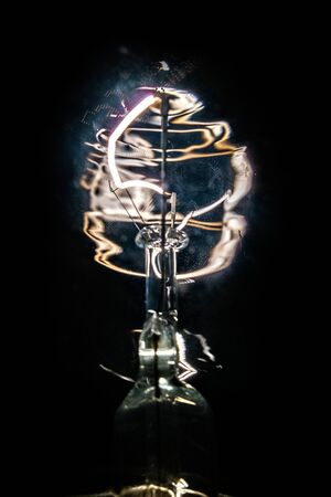 burning incandescent lamp with incandescent tungsten filament on a dark background
