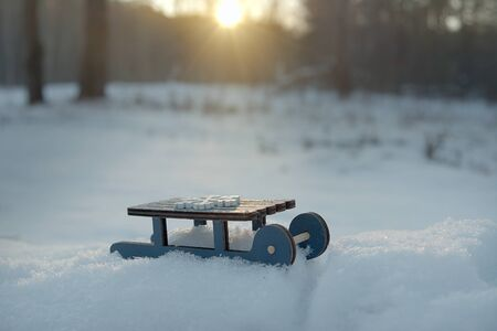 toy sleigh in winter on real snow on a Sunny frosty day, winter mood, Christmas card