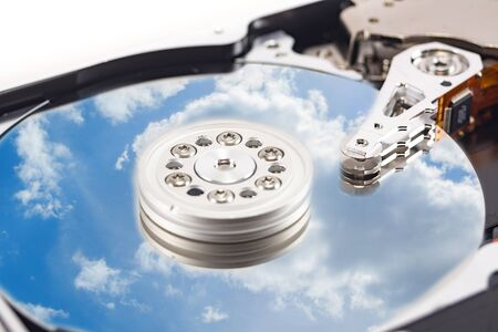 disassembled hard drive with the backdrop of clouds, the concept of cloud storage on white background, hdd, hard disk drive, close-up