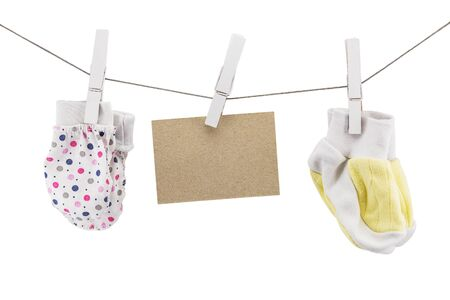 small mittens and socks for newborns on a rope with an empty sign, copyspace, mockup