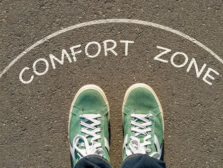photo on top of the sneakers and the inscription comfort zone on the asphalt, the concept of personal private space Foto de archivo