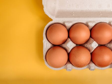 chicken eggs close-up on a yellow beautiful background in a cardboard box for transportation