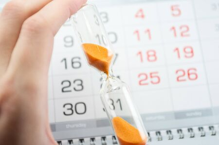 hourglass on the background of the calendar for the month, end of the month, deadline, reports, completion and delivery of works