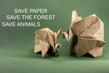 origami elephant and baby elephant made of Kraft paper on green background, paper and forest conservation concept, save paper save the forest, mockup, copy space Stock Photo