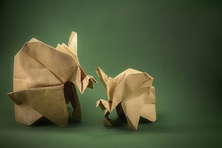 origami elephant and baby elephant made of сraft paper on green background, paper and forest conservation concept, save paper save the forest, mockup, copy space