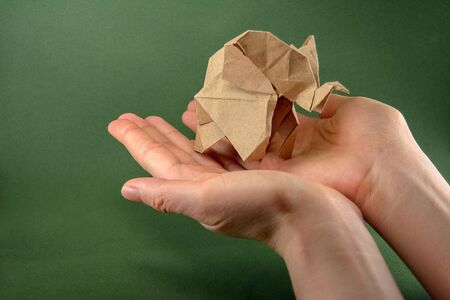 origami baby elephant craft paper on a green background on the hand, the concept of saving paper and forests, save paper, save the forest, mockup, copy space Stock Photo