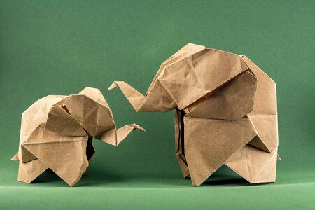 origami elephant and baby elephant made of craft paper on green background, paper and forest conservation concept, save paper save the forest, mockup, copy space