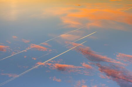 the sun shining through the clouds against the blue sky, light clouds in the sky, traces of aircraft, top view