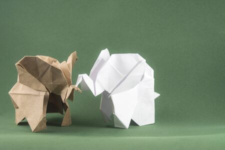 origami baby elephants made of craft paper on green background, paper and forest conservation concept, save paper save the forest, protect the animals, mockup, copy space Stock Photo