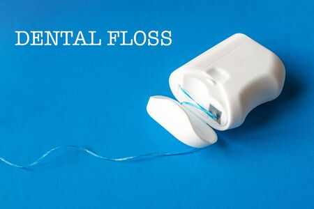 dental floss on a blue background, the concept of care for the oral cavity, preventing tooth decay, copyspace
